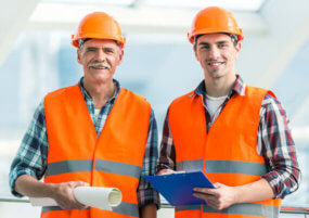 Pay As You Go Telephone Call Answering services Two men in high visibility PPE holding a clipboard and roll of paper